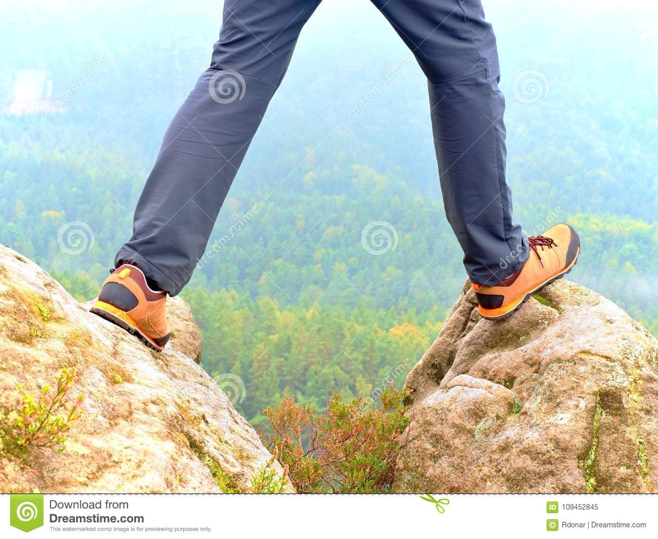 Hiker legs in comfortable trekking boots on rock. Man legs in light outdoor trousers, leather shoes