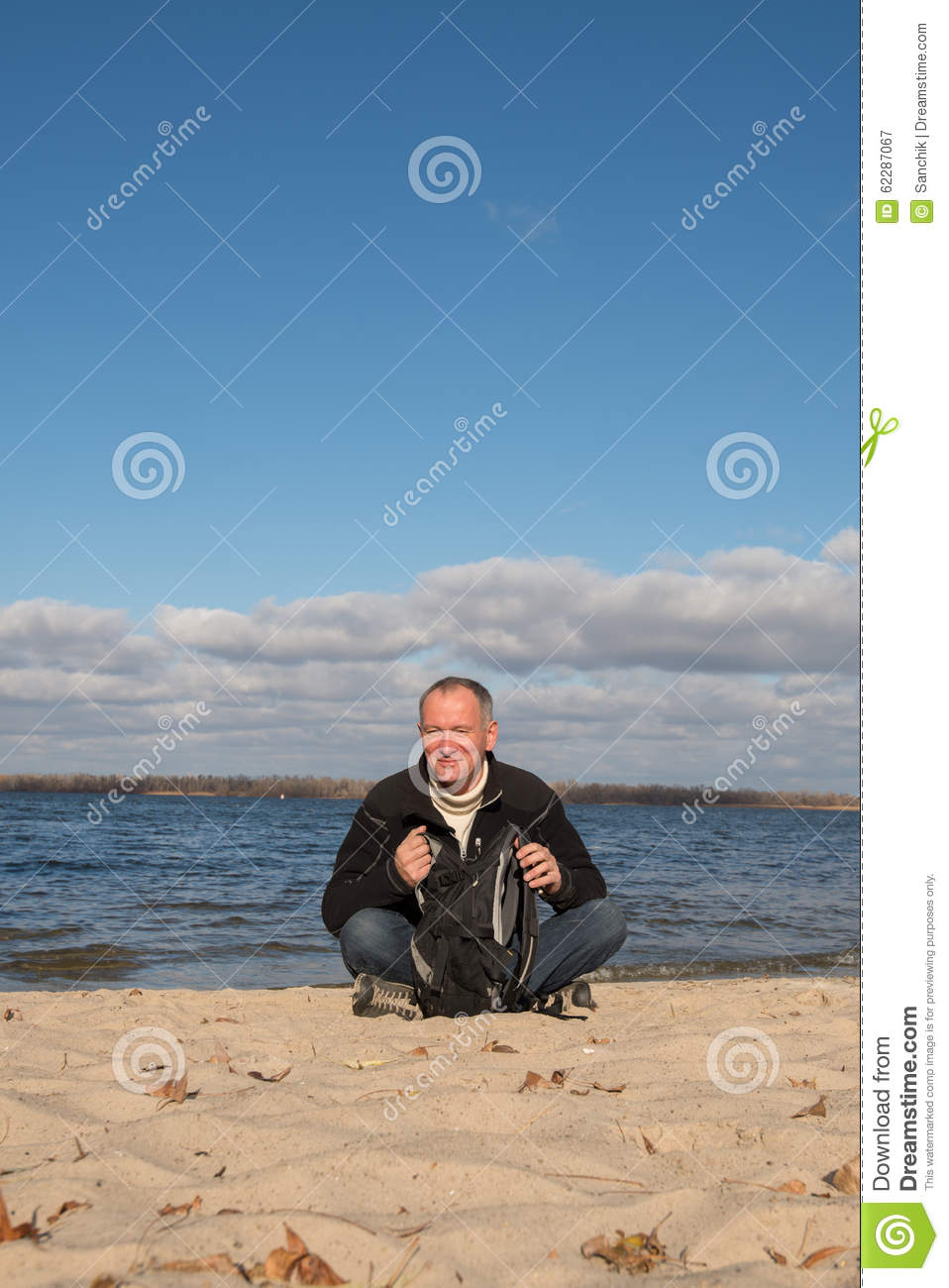 Hiker man resting on the coast, smiling looking at the contents