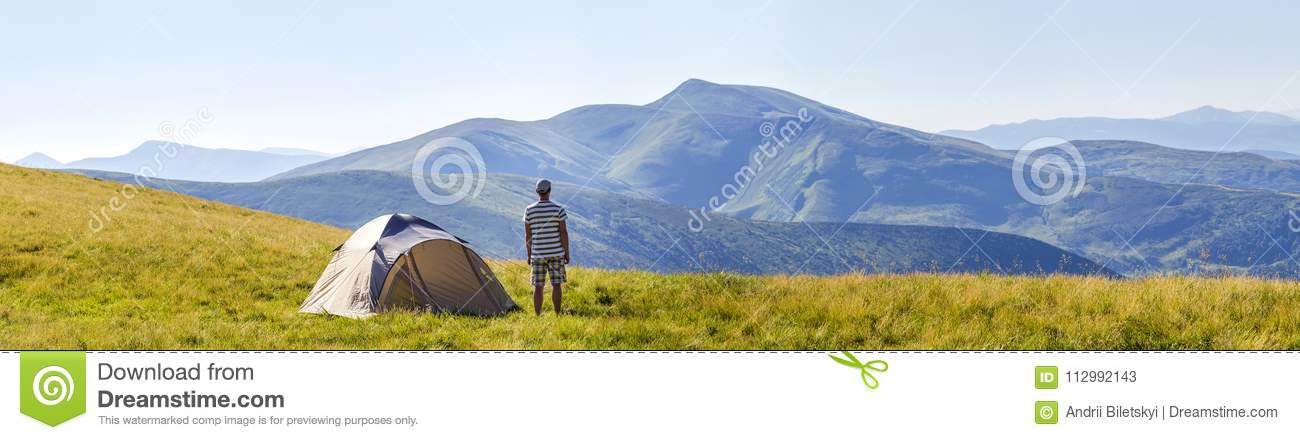 Hiker man standing near camping tent in carpathian mountains. To