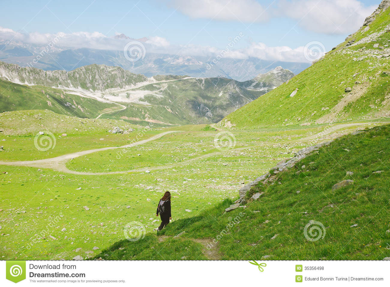Hiker woman walking on forest road in les Alps, France.
