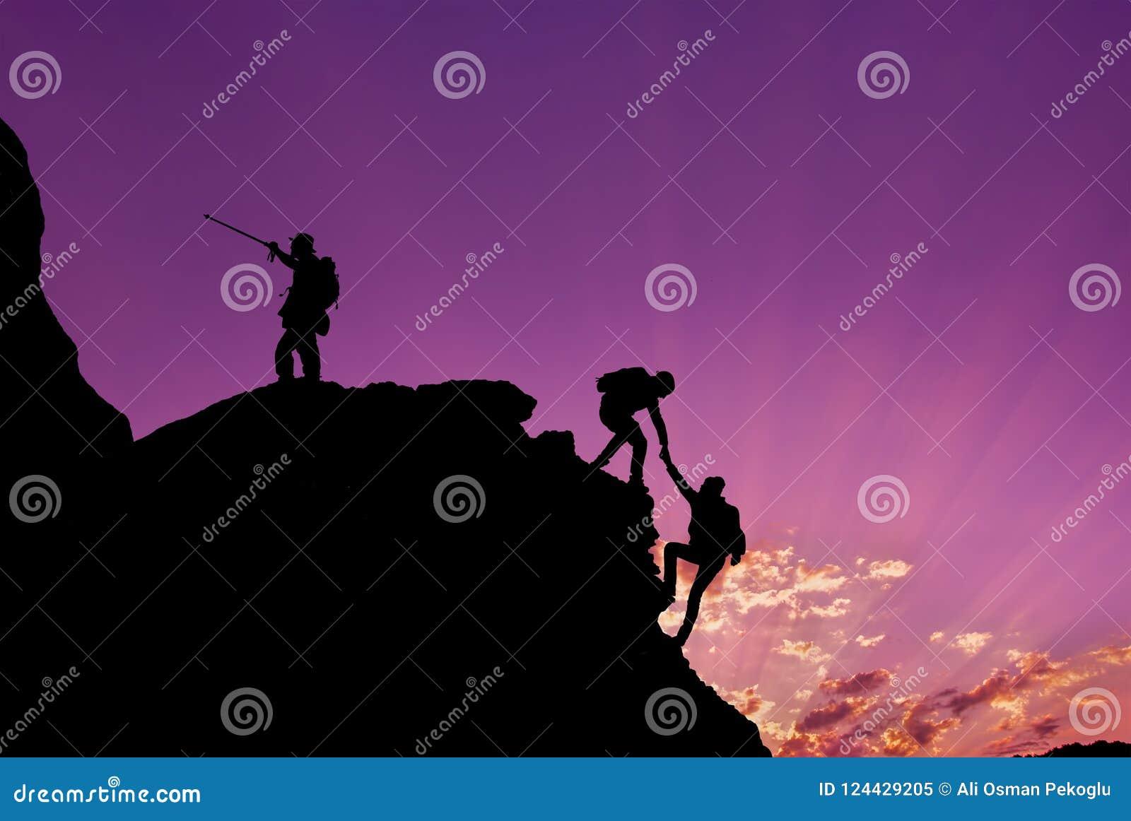 Hikers взбираясь на утесе, горе на заходе солнца, одном из их давая руку и помогая взобраться Сыгранность, помощь, успех, победит
