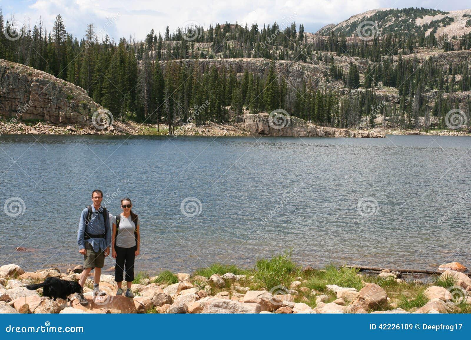 Hikers в горах отдыхают на озере