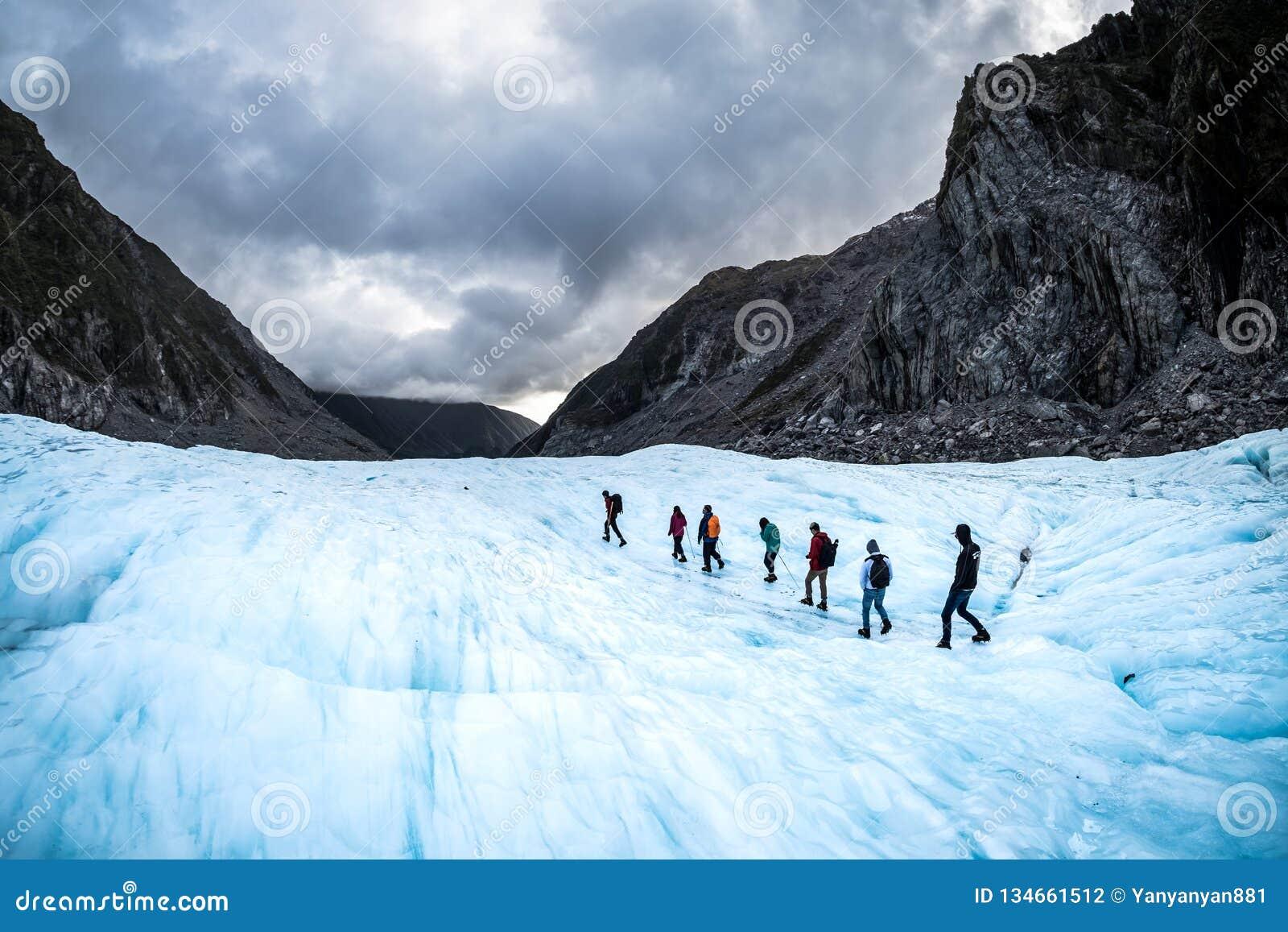 Hikers и путешественники идя на лед в леднике Fox, Новой Зеландии