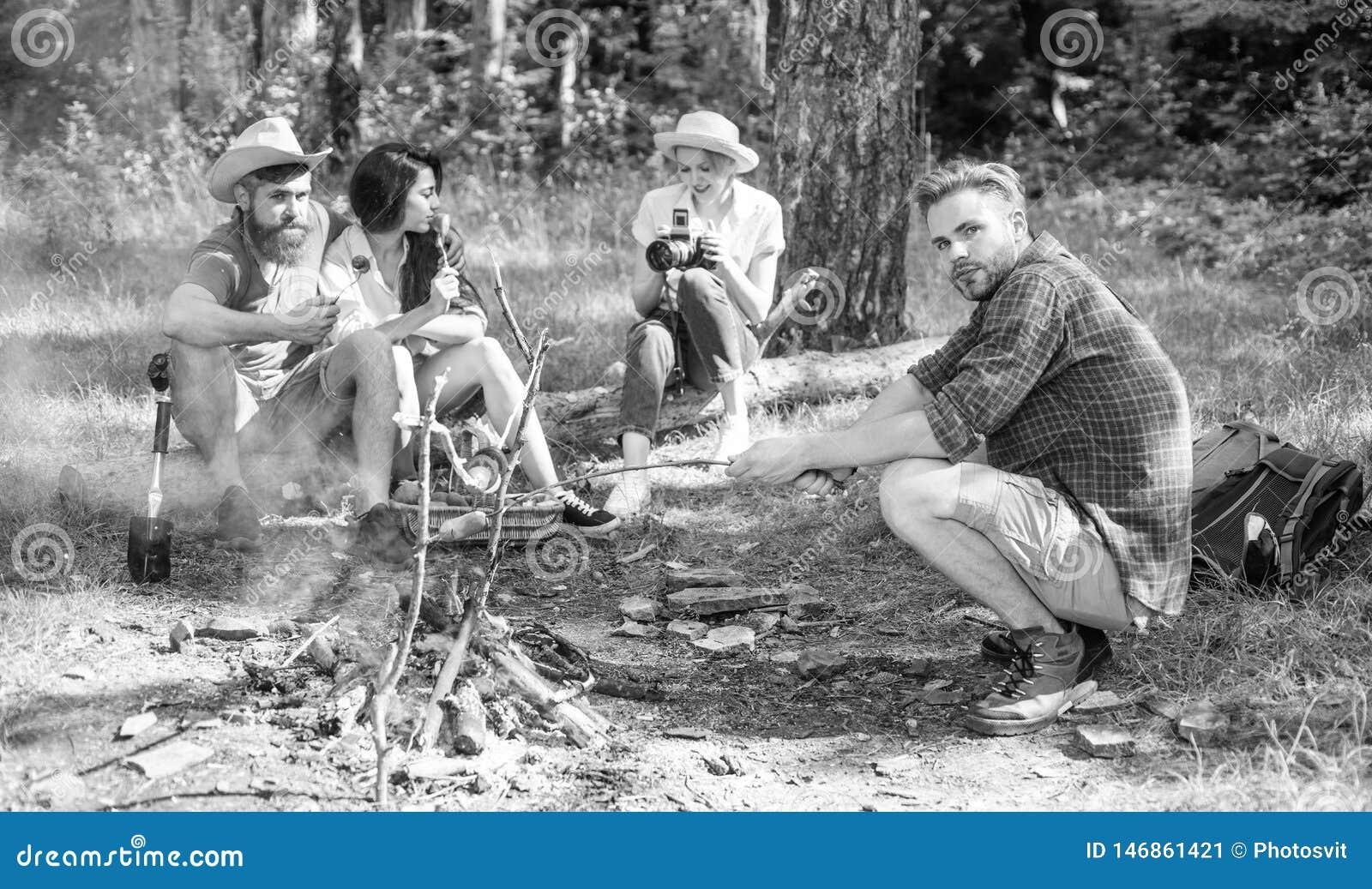 Hikers сидят около лагерного костера ослабляя пока еда жарить в духовке ожидания Hikers организовали быстрый пикник для еды и для
