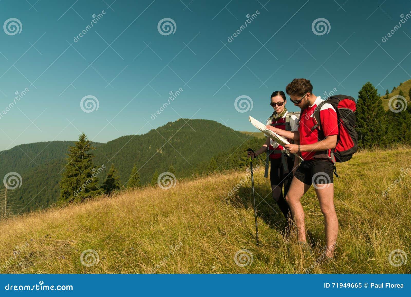 Hikers советуя с картой
