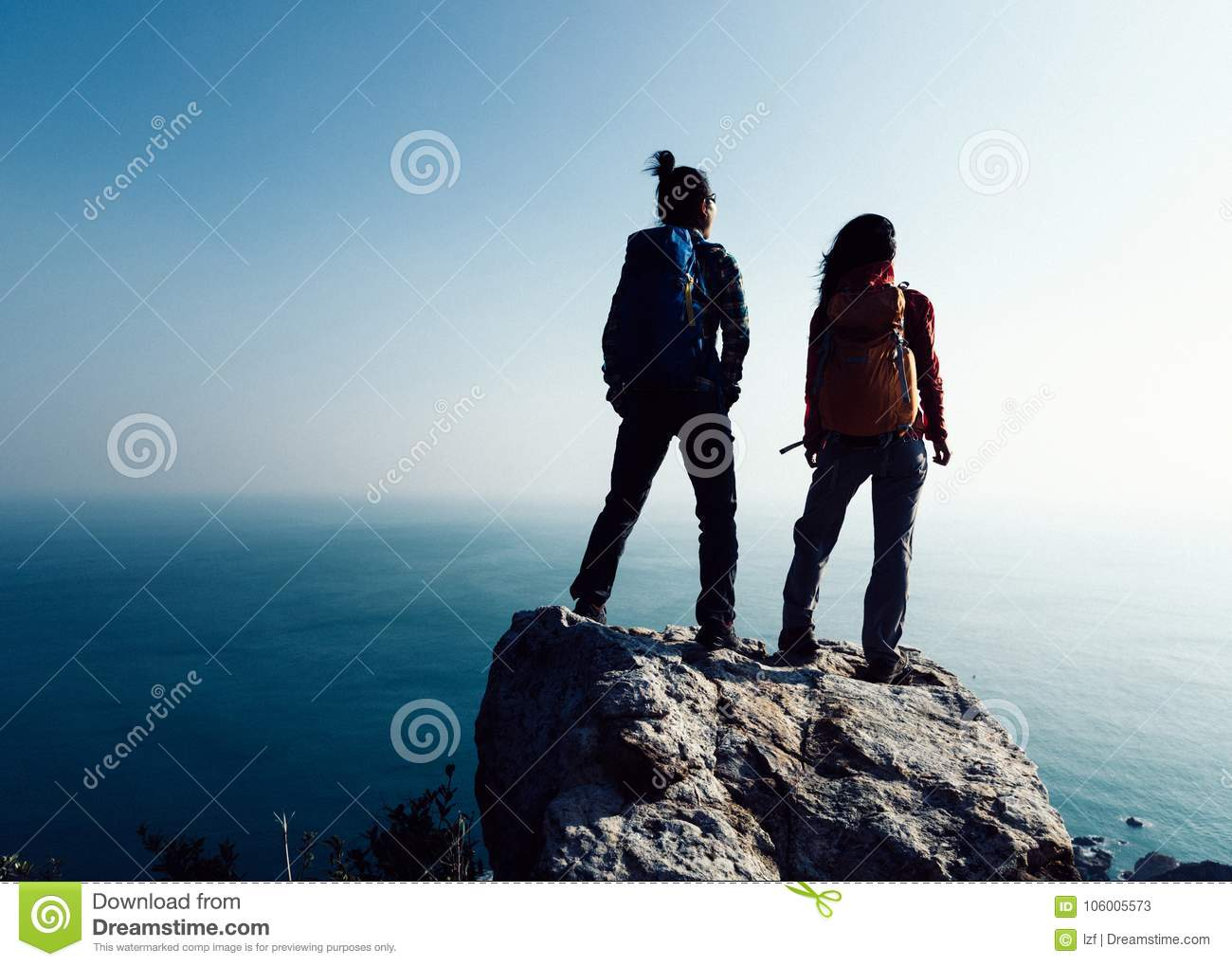 Hikers looking at the view on seaside mountain top rock edge