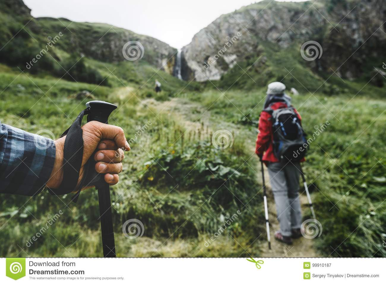 Hikers In The Mountains, Trekking Pole In The Hand Of A Traveler Person Close-up. Travel Lifestyle Vacation Concept
