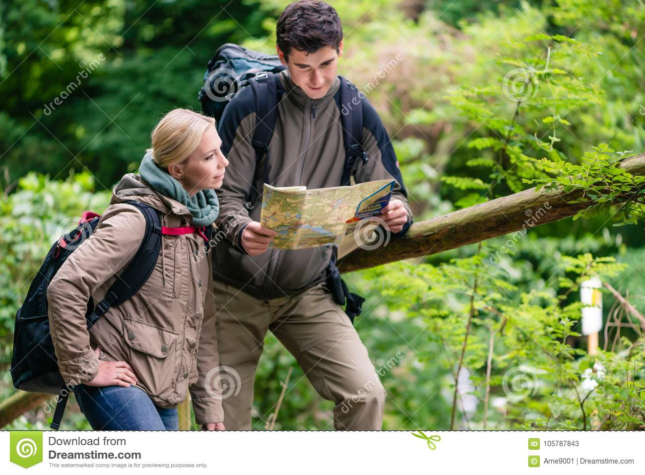 Young hikers orientating with trail map