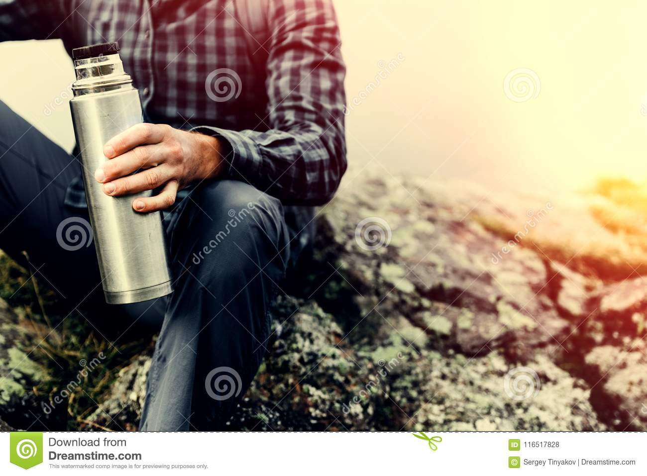 Hiking Adventure Tourism Concept. Unrecognizable Hiker Man Holding Thermos In His Hand, Close-up Toned Image