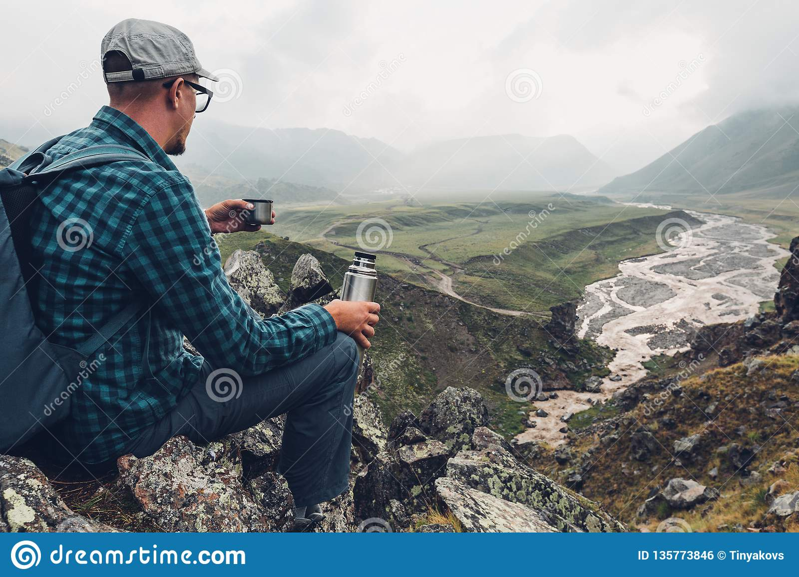 Hiking Adventure Tourism Vacation Holiday Concept. Young Traveler Holding Thermos In His Hand And Enjoy View Valley, Rear View