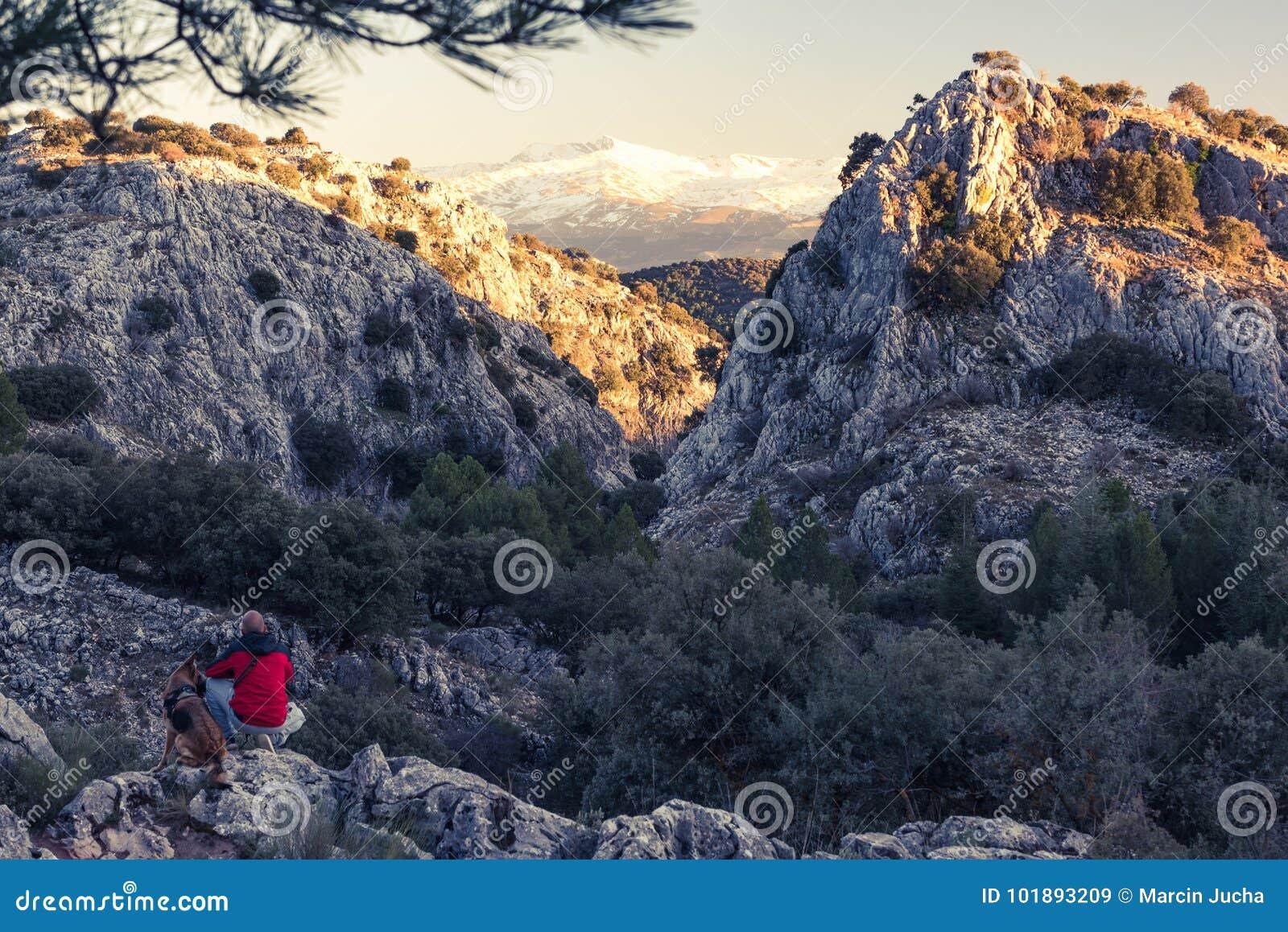 Hikker con il cane muggito in alte montagne