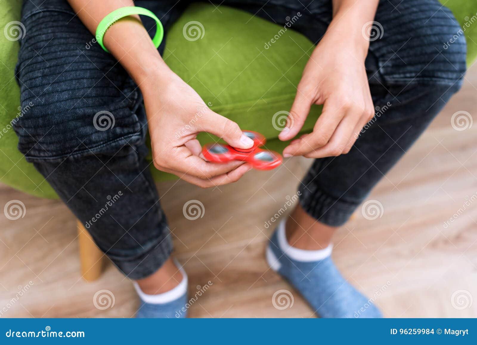 Hilandero de la persona agitada Hilandero rojo de la mano, juguete de la mano que inquieta que gira en la mano del ` s del niño A