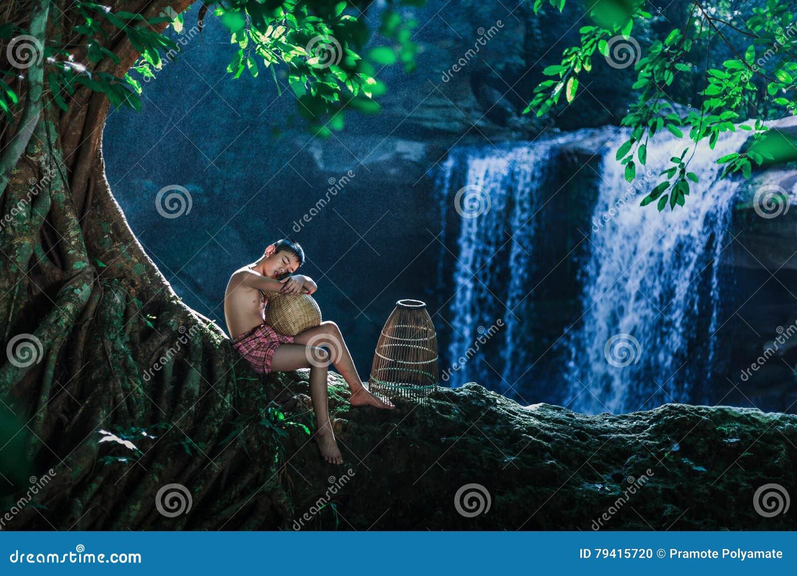 Hildren in rural sit under a tree on the rocks in a waterfall.