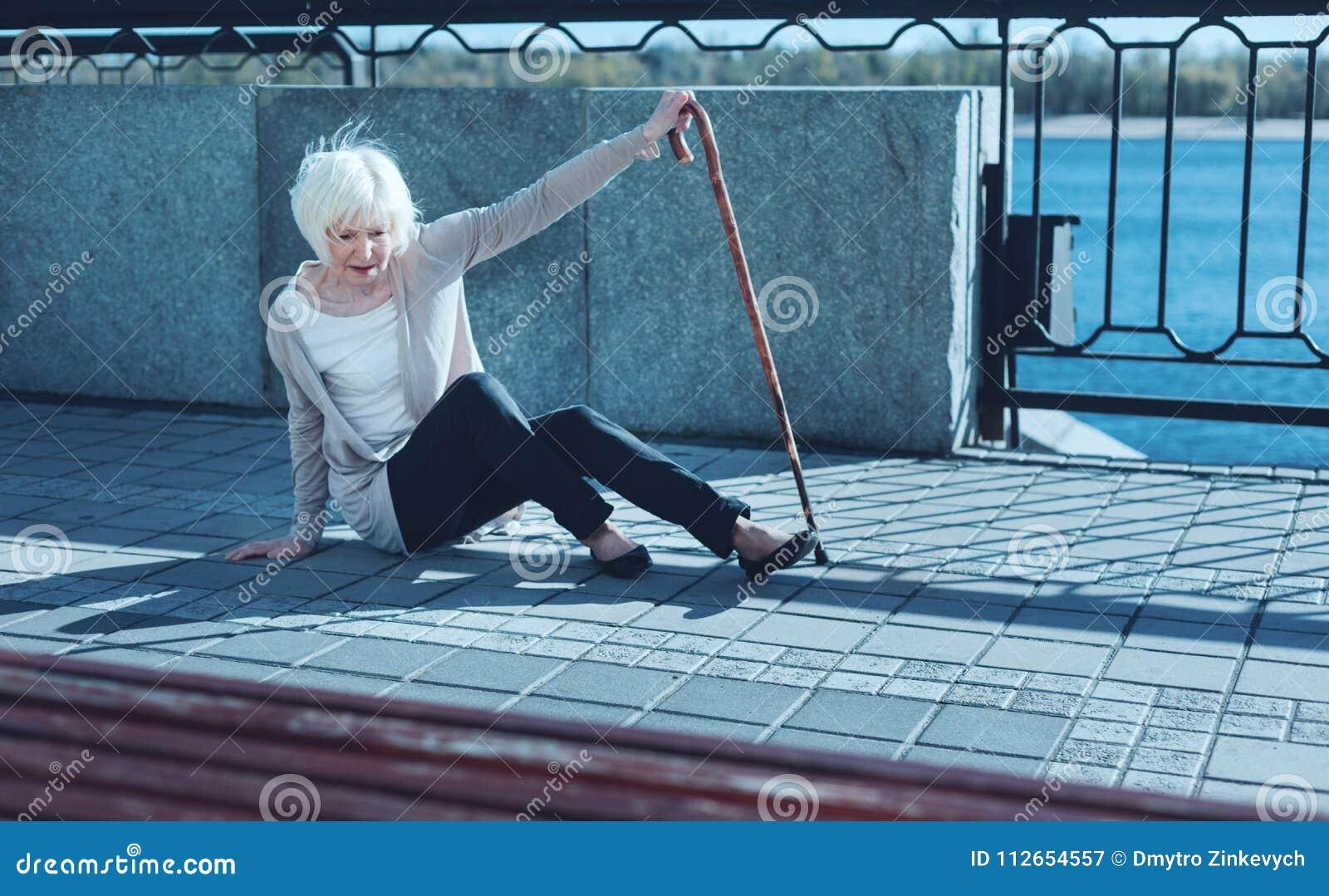 Hilflose ältere Dame, die unter Übelkeit leidet