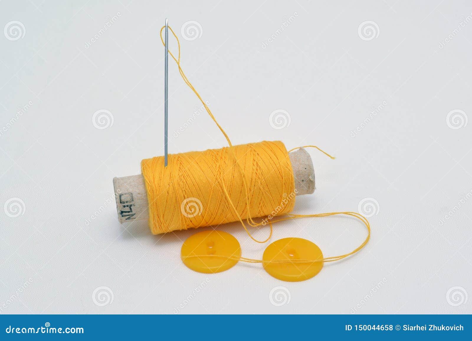 Hilo amarillo con la aguja y botones amarillos