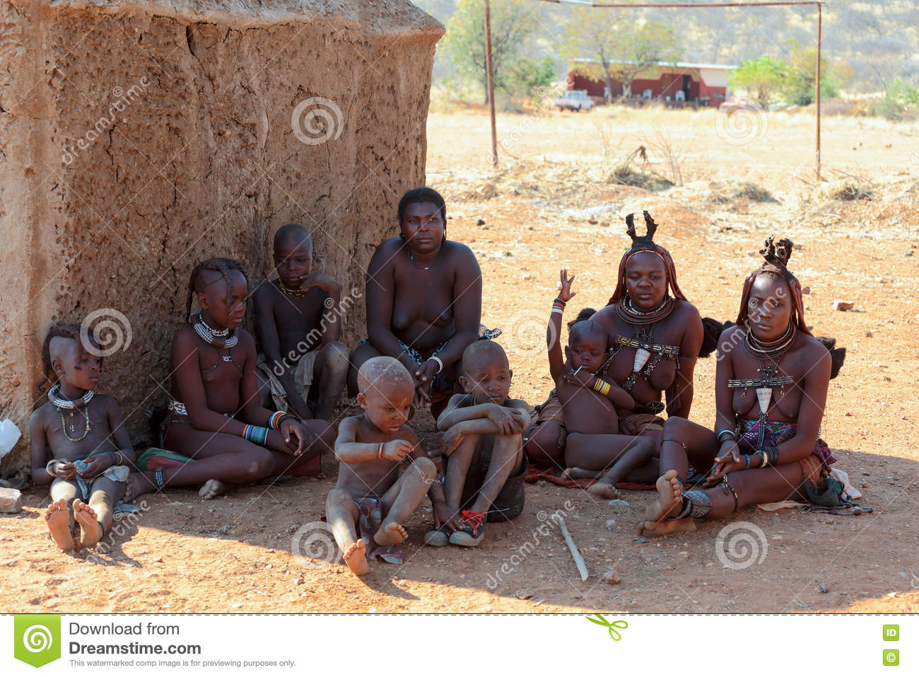 Himba woman and children working carrying water to a