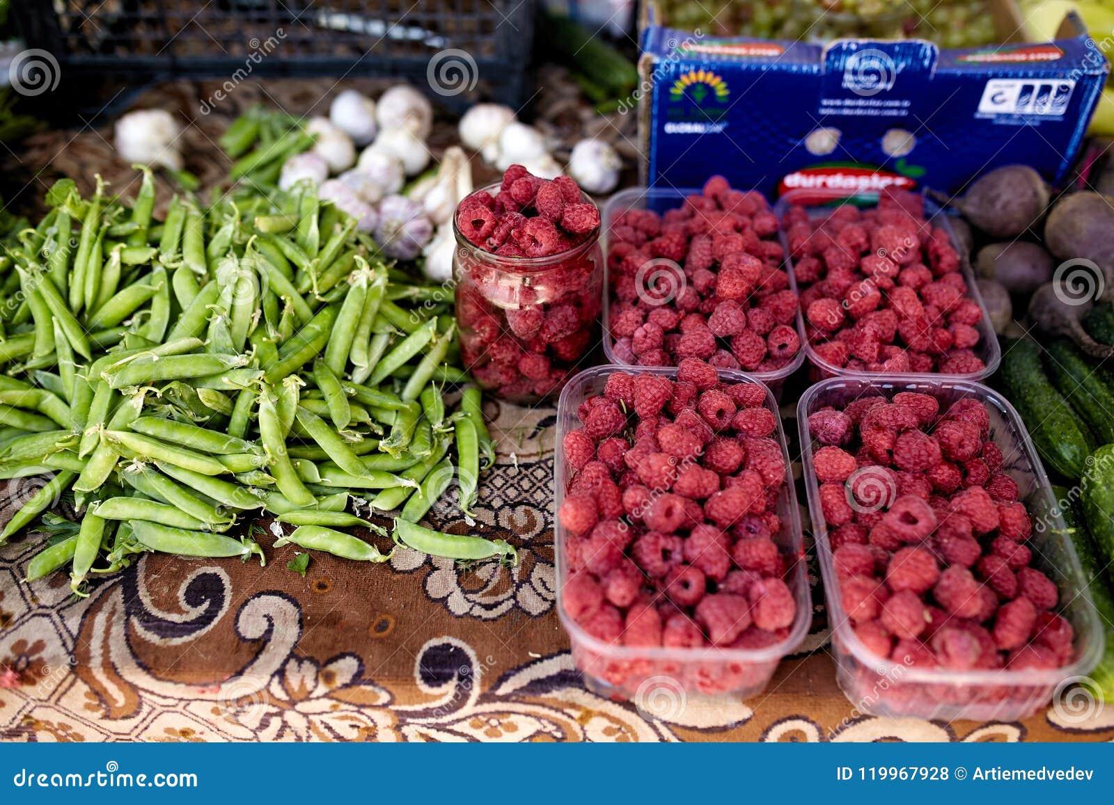Himbeeren, Knoblauch und Erbsen auf einem Bauernhofmarkt in der Stadt Obst und Gemüse an einem Landwirtsommermarkt