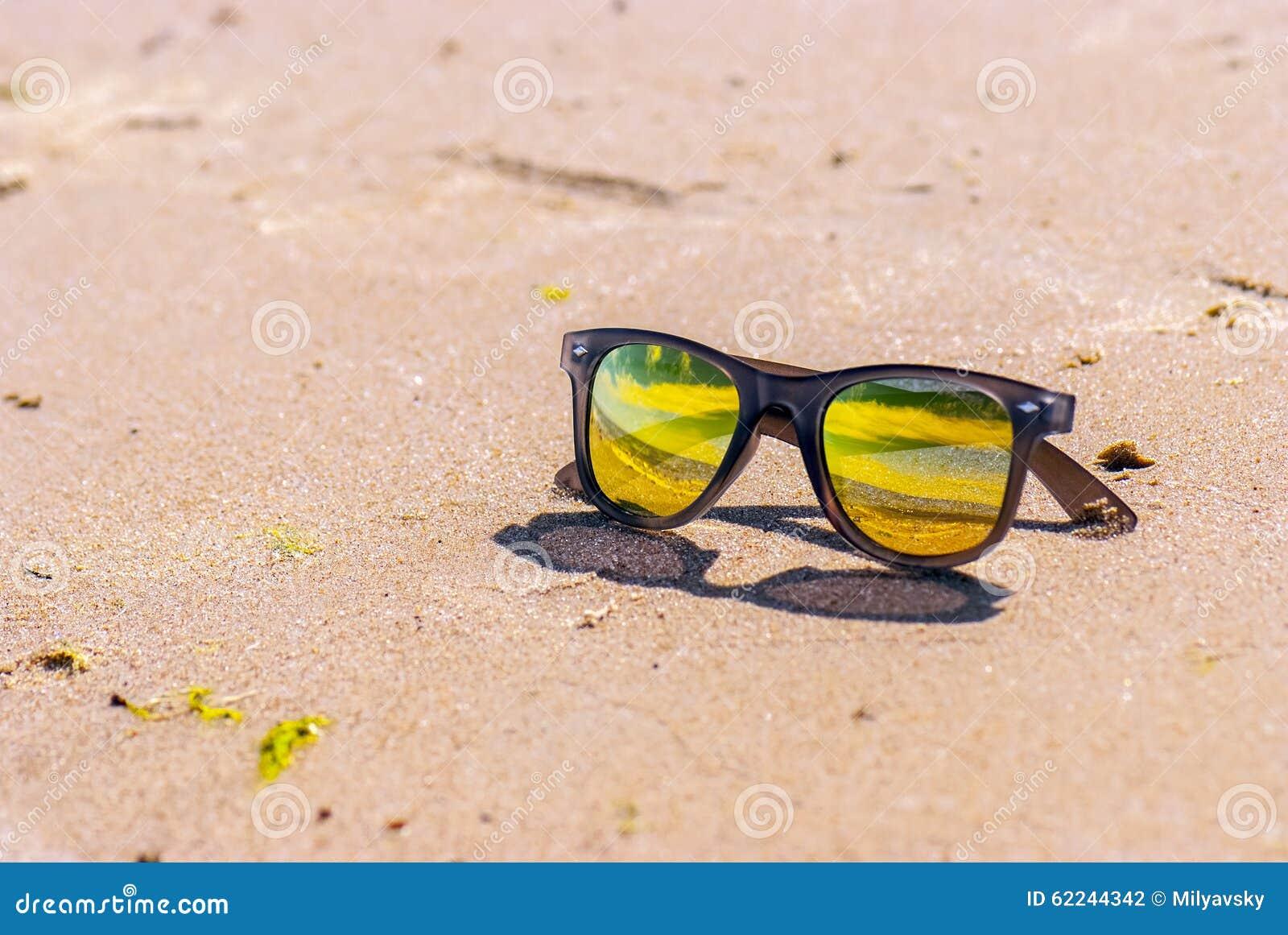 Himmel reflekteras i solglasögon, strand