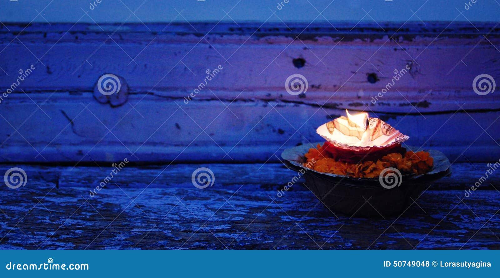 Hinduism religious ceremony puja flowers and candle near river Ganga, Varanasi, Uttar Pradesh, India.