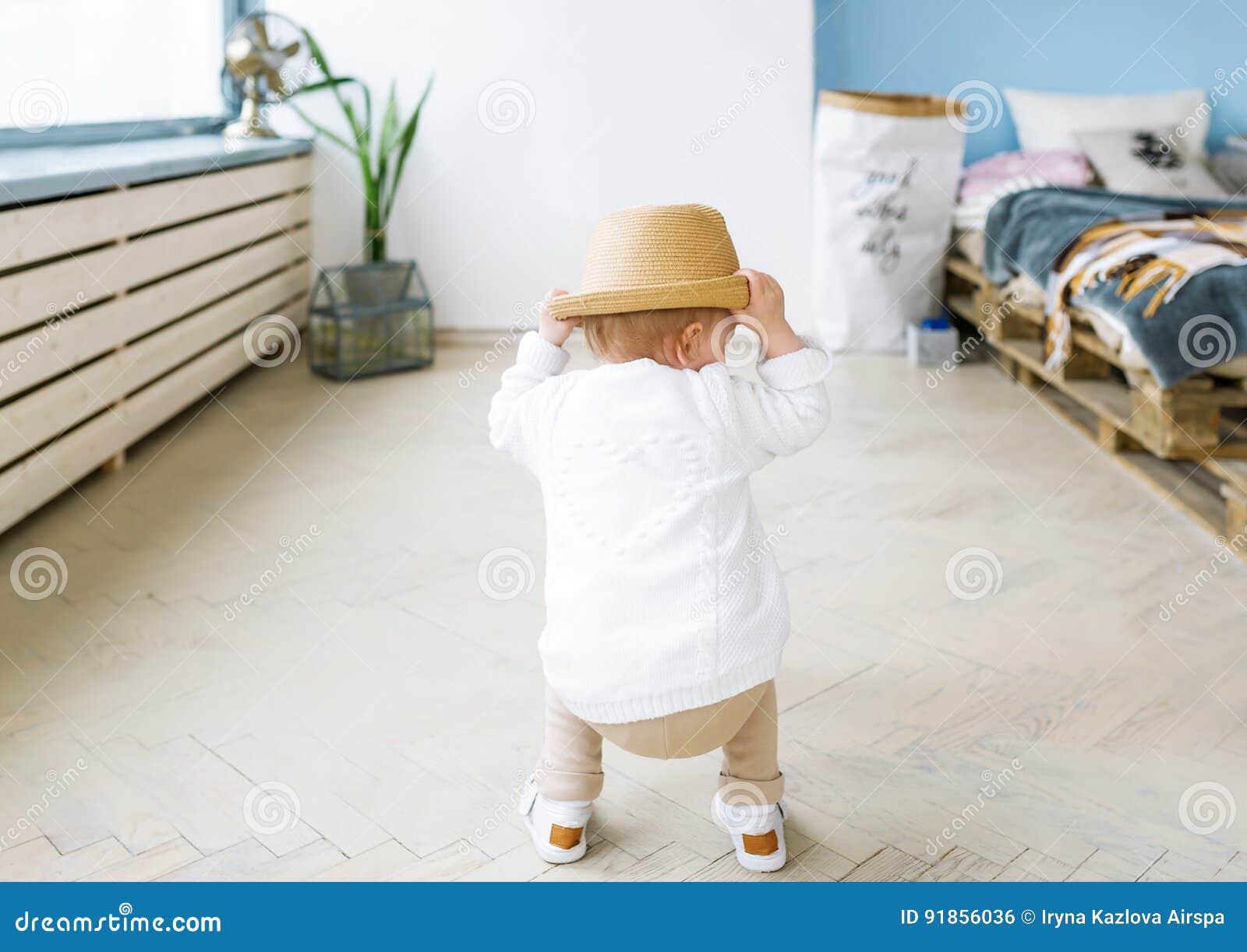 Hintere Ansicht über ein kleines Mädchen in einem Strohhut Das Baby spielt im hellen Raum, zuhause