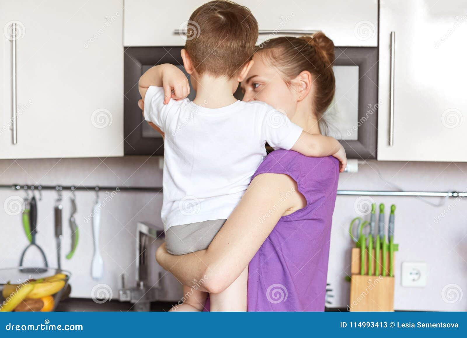 Hintere Ansicht der jungen dünnen Mutter hält Sohn auf Händen, Stand an der Küche gegen die modernen Möbel und geht, das Abendess