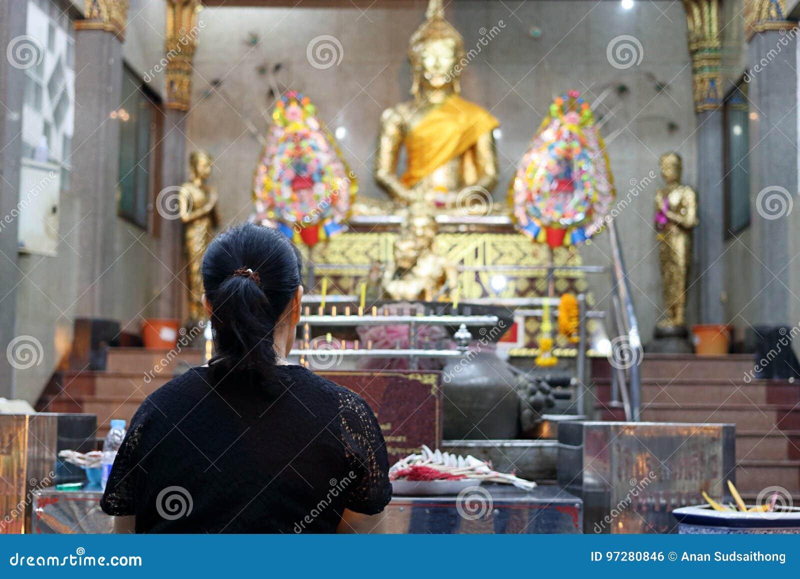 Hintere Ansicht der thailändischen Frau betend zu Buddha im Tempel