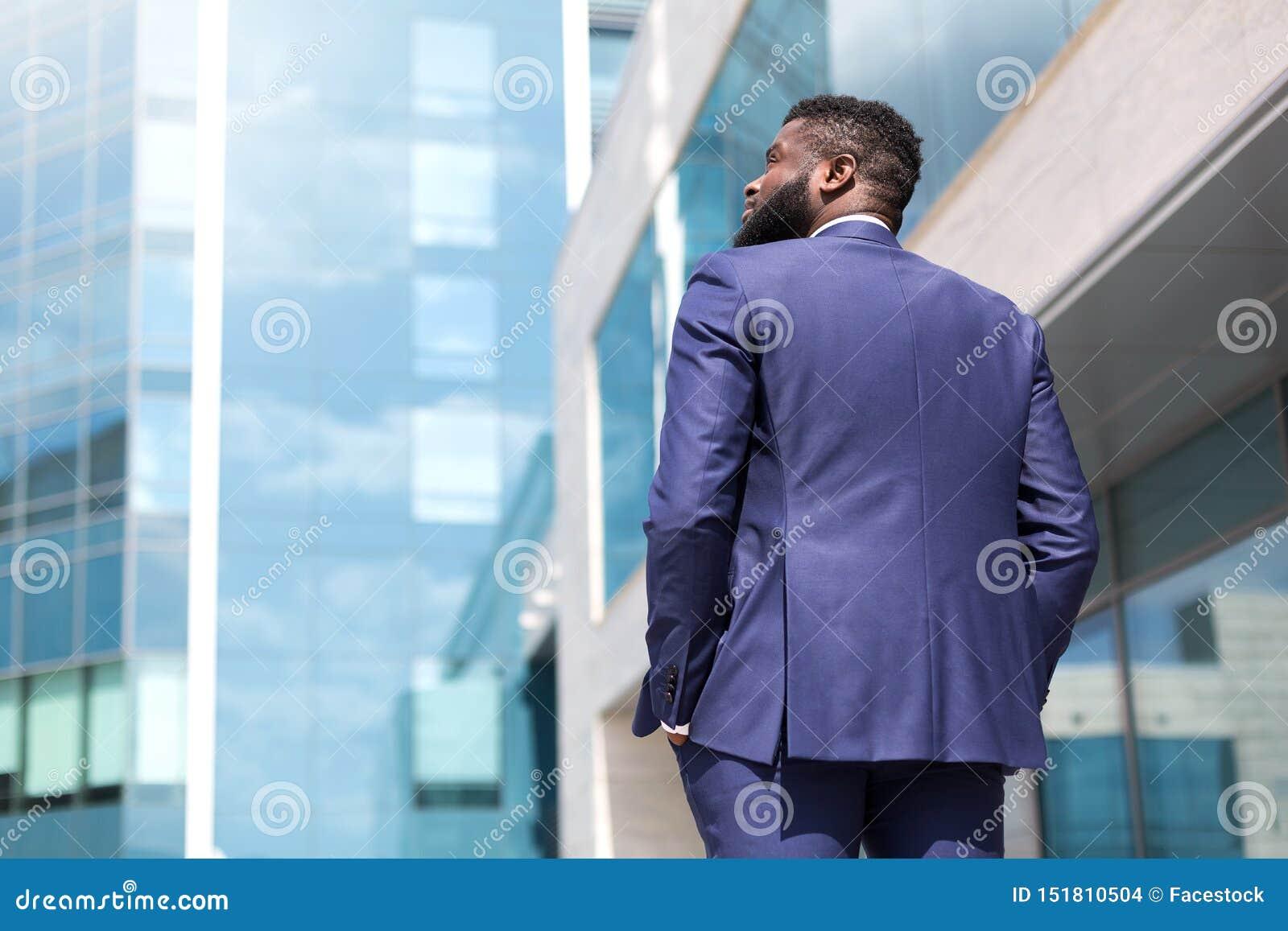 Hintere Ansicht des Afroamerikanergeschäftsmannes draußen gehend entlang große Bürofenster Geschossen von der R?ckseite Abschluss