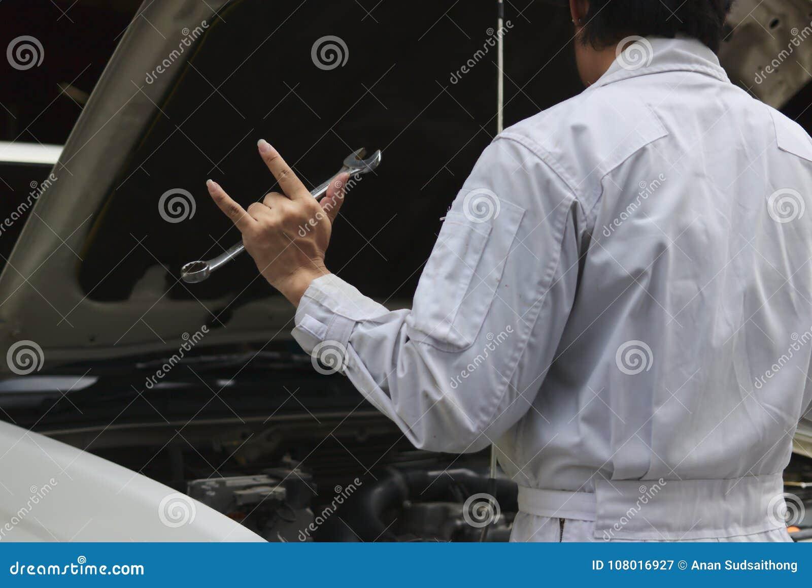 Hintere Ansicht des Berufsmechanikermannes, der ich liebe dich Schlüssel und seine Hand mit Zeichen mit Auto in der offenen Haube