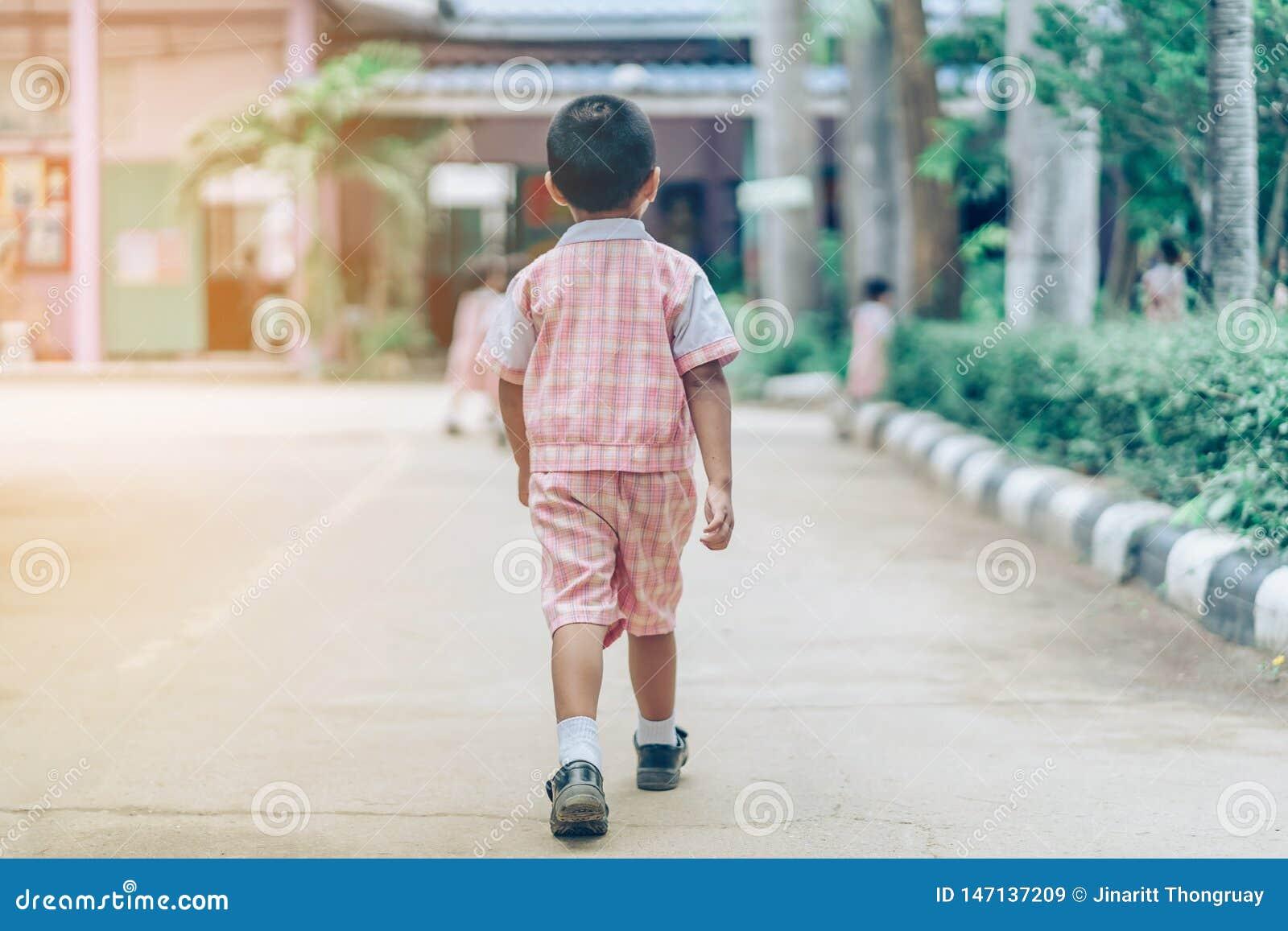 Hintere Ansicht des Jungen folgte Freundinnen auf Straße, um zum Klassenzimmer zu gehen