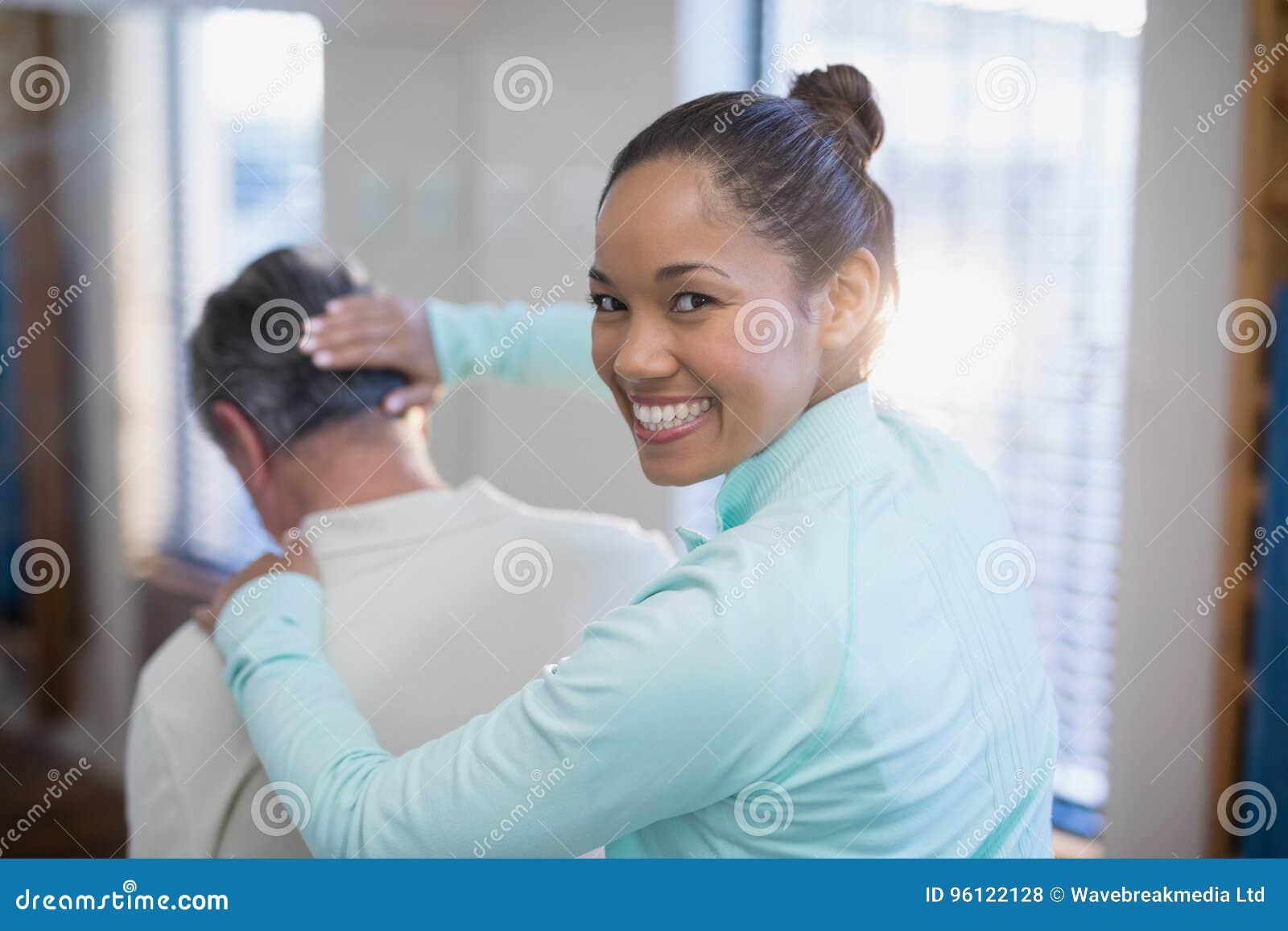 Hintere Ansicht des Porträts des lächelnden weiblichen Therapeuten, der dem älteren männlichen Patienten den Hals massiert gibt