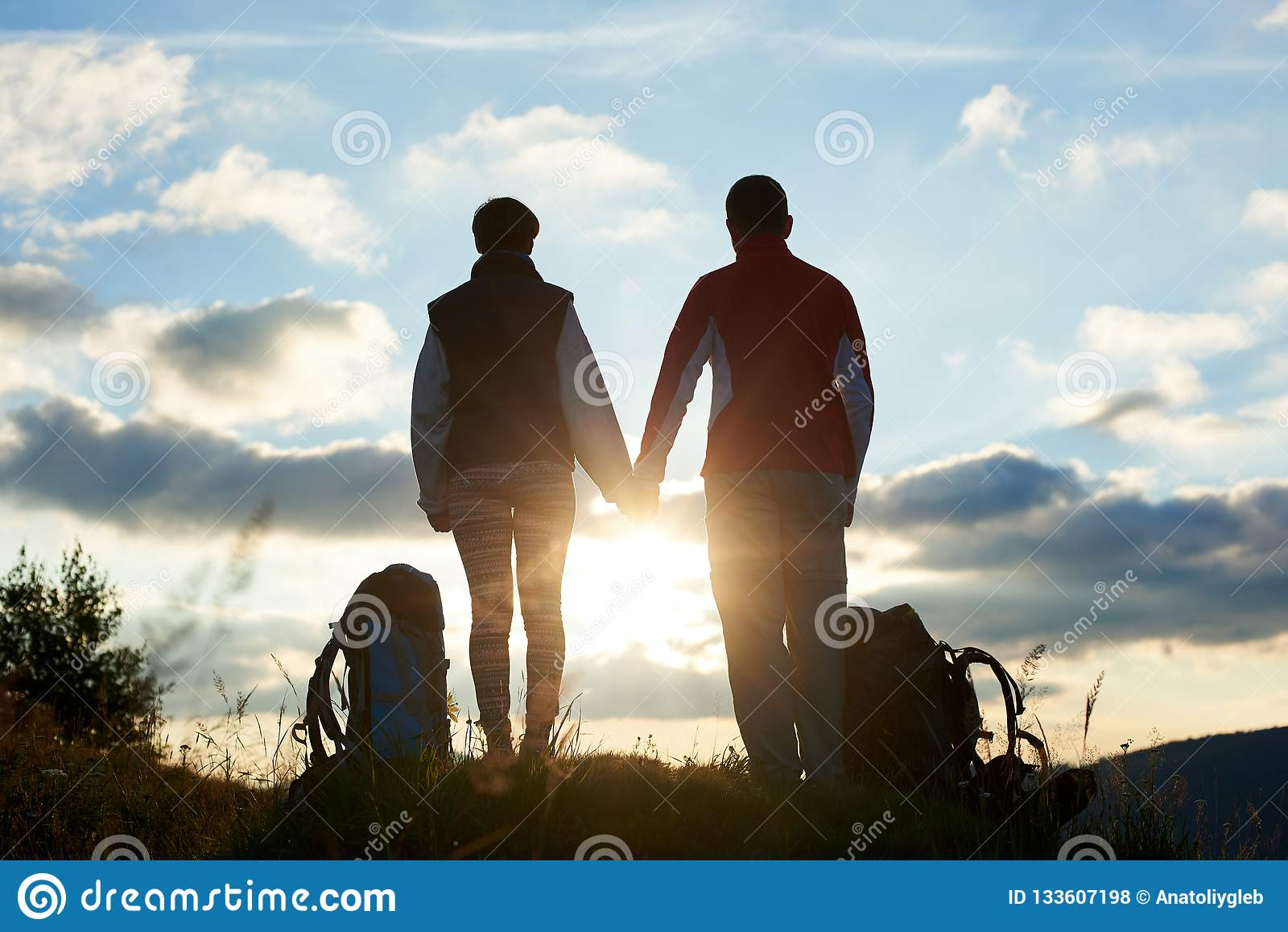 Hintere Ansicht von den Jugendlichen, die den Sonnenuntergang im Gebirgshändchenhalten bewundern