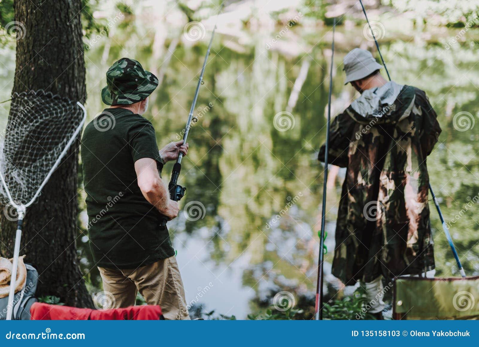 Hintere Ansicht von den Männern, die auf der Flussbank fischen