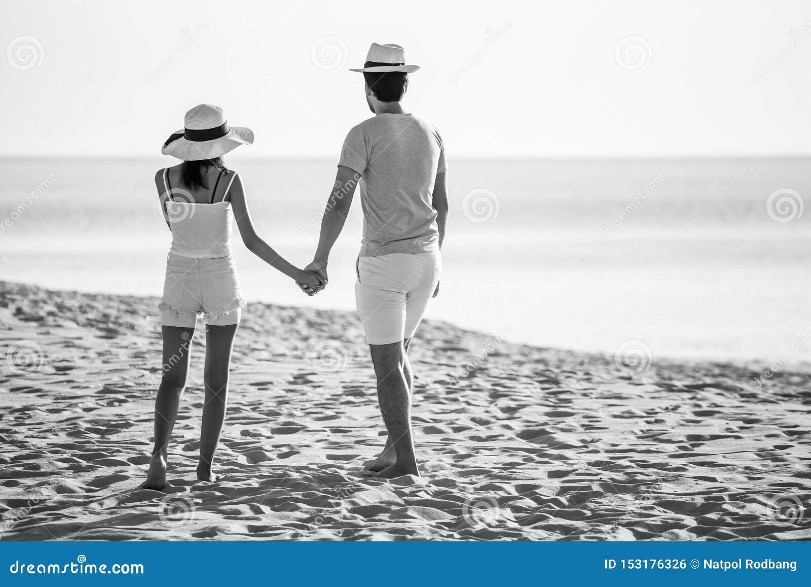 Hintere Ansicht von jungen Paaren in der Liebe, welche die Zukunft schaut und Hand am Seestrand zusammenhält gl?ckliche l?chelnde