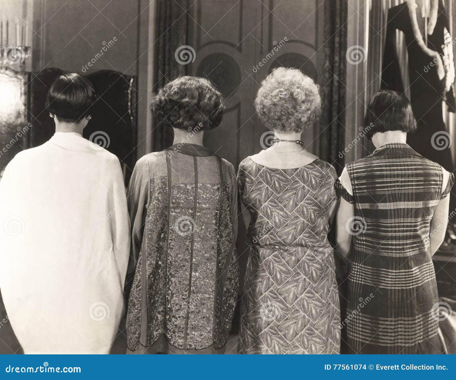Hintere Ansicht von vier Frauen, die in Folge stehen