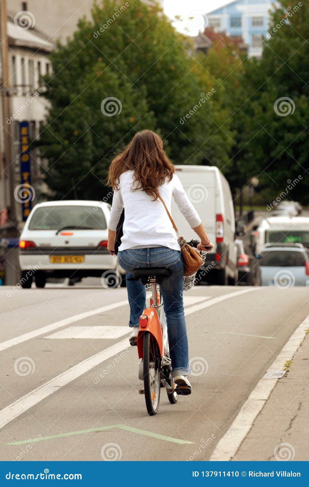 Hintere Frau, die ein Fahrrad in der Stadt reitet