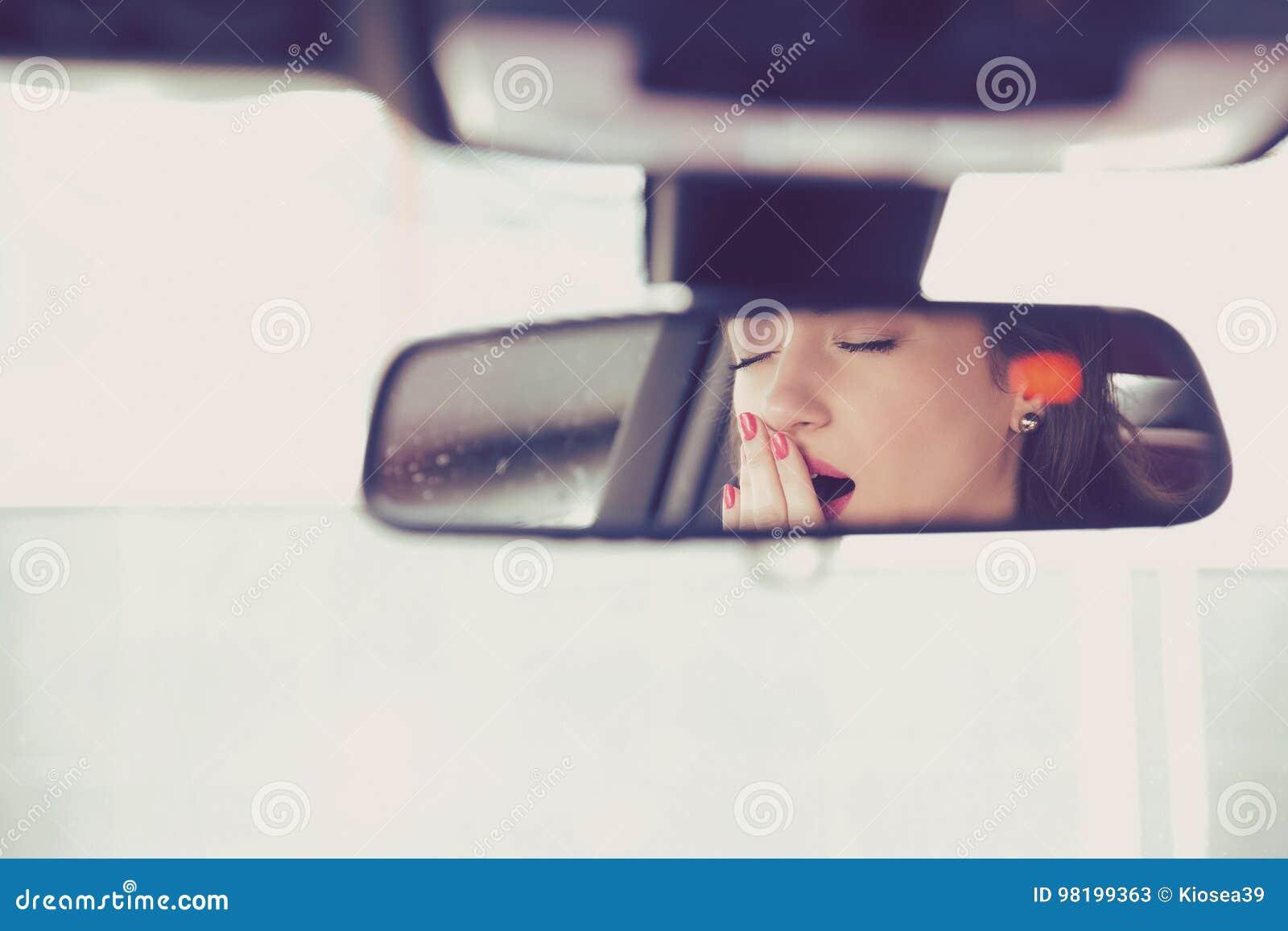 Hintere Spiegelansicht einer schläfrigen gähnenden Frau, die ihr Auto nach Antrieb der langen Stunde fährt
