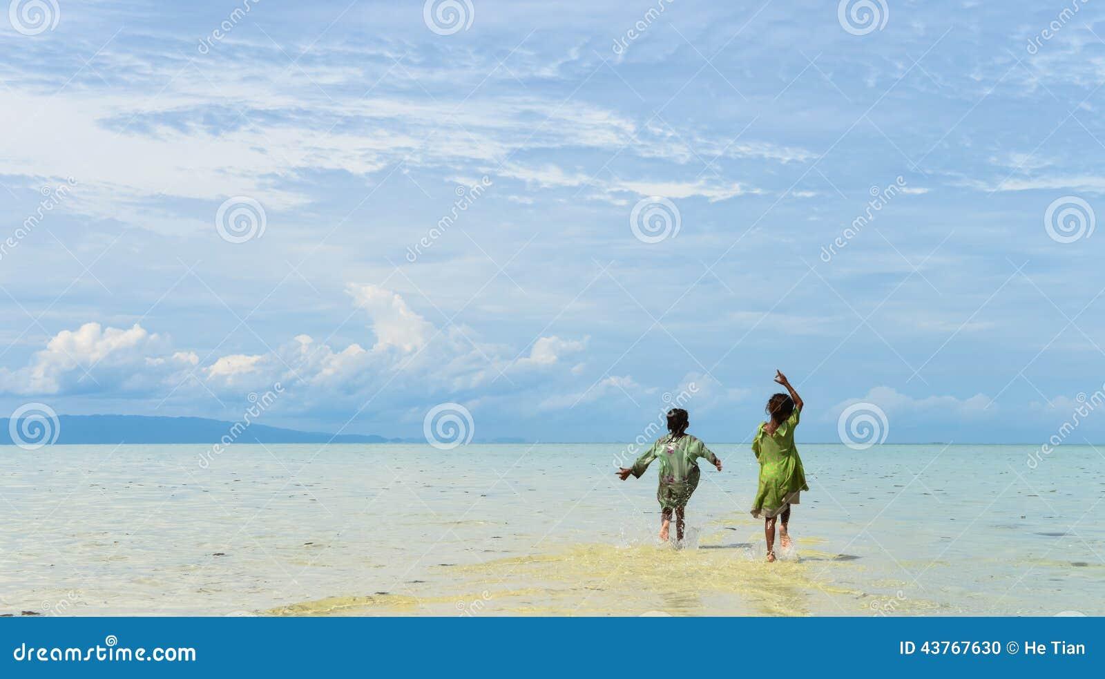 Hinteres Porträt von zwei gebürtigen jungen Schwestern, die in das seichte Wasser auf tropischem Strand laufen und springen