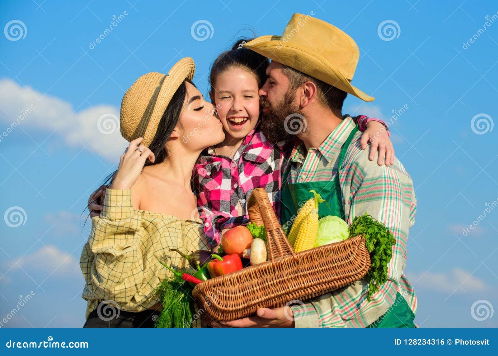 Hintergrund des blauen Himmels der Familiengärtnerkorbernte Familiengartenarbeit Familienbauernhofkonzept Eltern und Tochterlandw