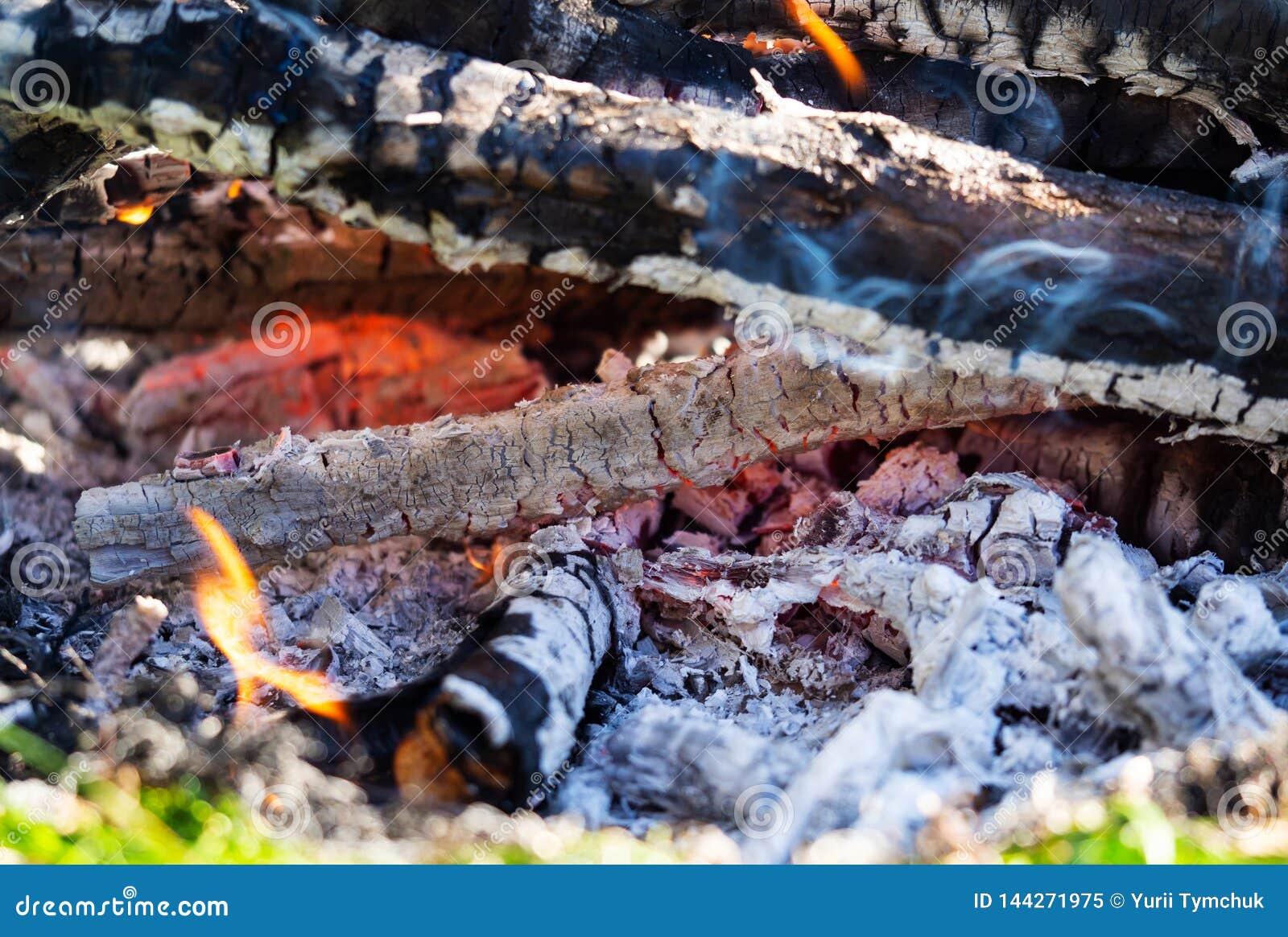 Hintergrund des Kamins mit dem Mit Handschuhen bekleiden der Glut Schließen Sie herauf Ansicht über schwelend Feuer Glut, die mit