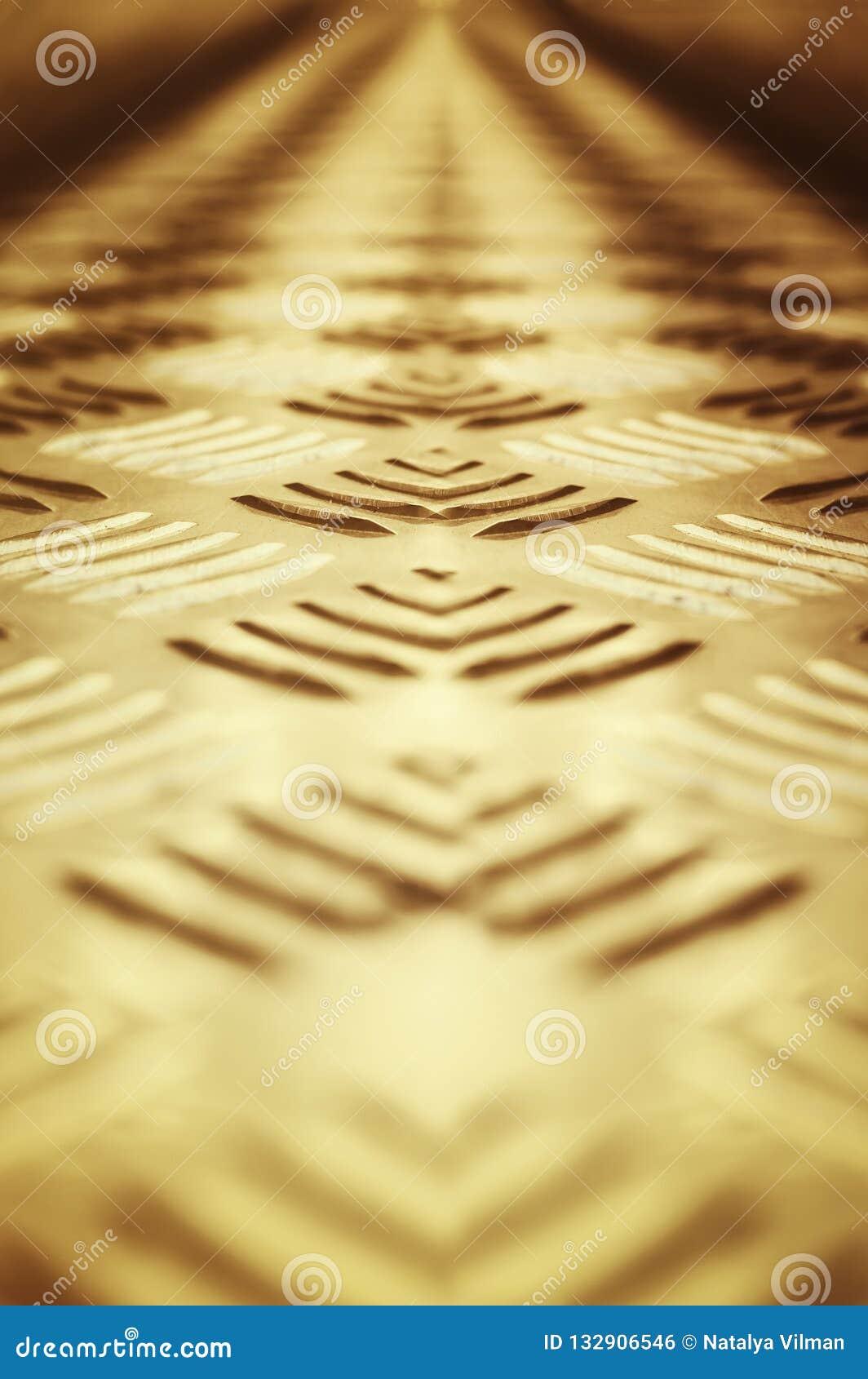 Hintergrund des Metalls mit einem wiederholenden Muster der Bronzefarbe Nahaufnahme, selektiver Fokus