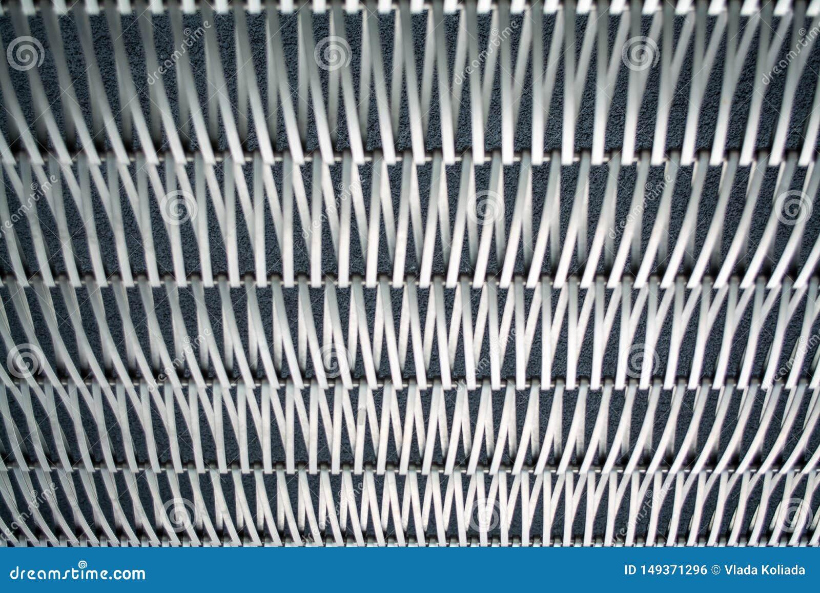 Hintergrund oder Beschaffenheit auf einer grauen Wand ein Gitter vom Metall ein Draht, die unter selbst sich verflechten Haken un