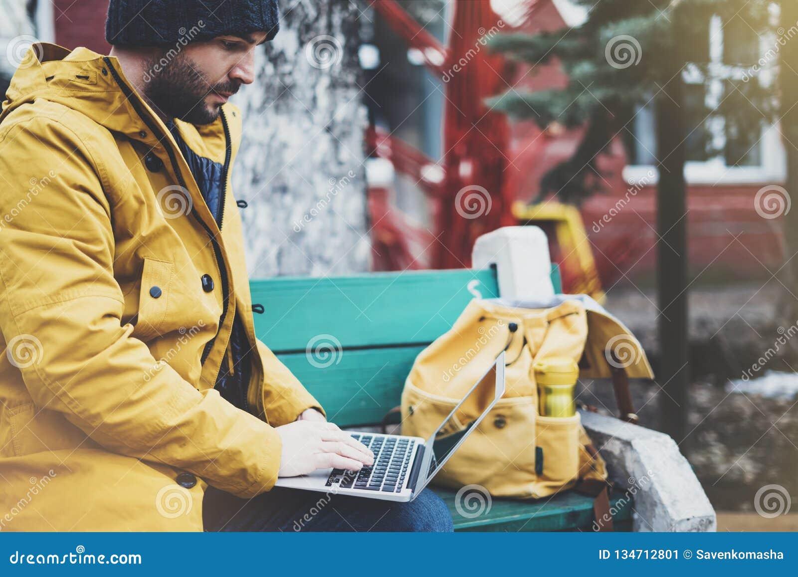 Hippie avec le sac à dos jaune, veste, chapeau, tasse de café thermo utilisant la rue ouverte d ordinateur portable d ordinateur