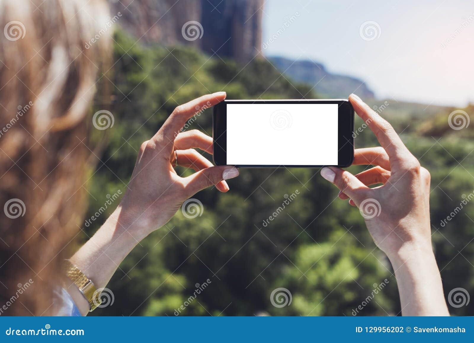 Hippie Bloggermädchen hält Handy in den weiblichen Händen, machen Fotophoto von Naturlandschaft auf einer sonnigen Sommertagesrei