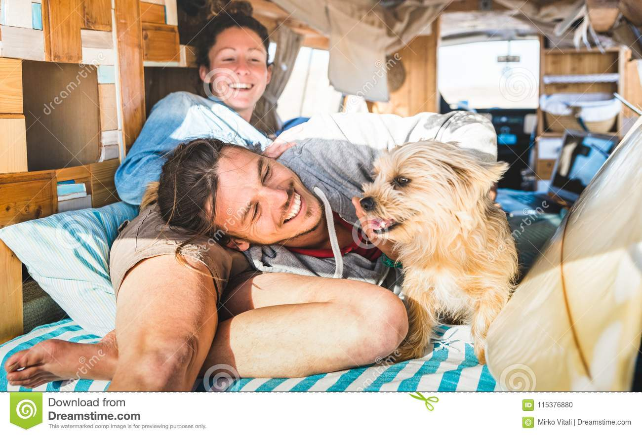 Hippie couple with funny dog traveling together on vintage minivan transport - Life inspiration concept with indie people on mini