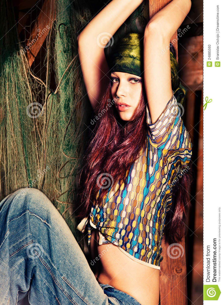 Girl in hippie style clothes in fisherman's cottage.
