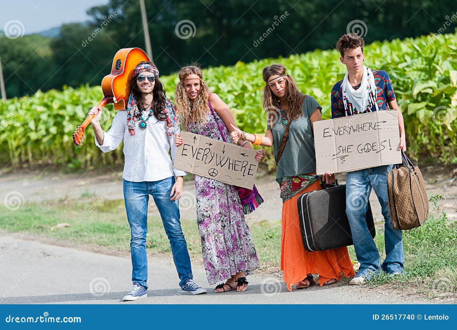 Hippie-Gruppe, die auf einer Landschafts-Straße per Anhalter fährt