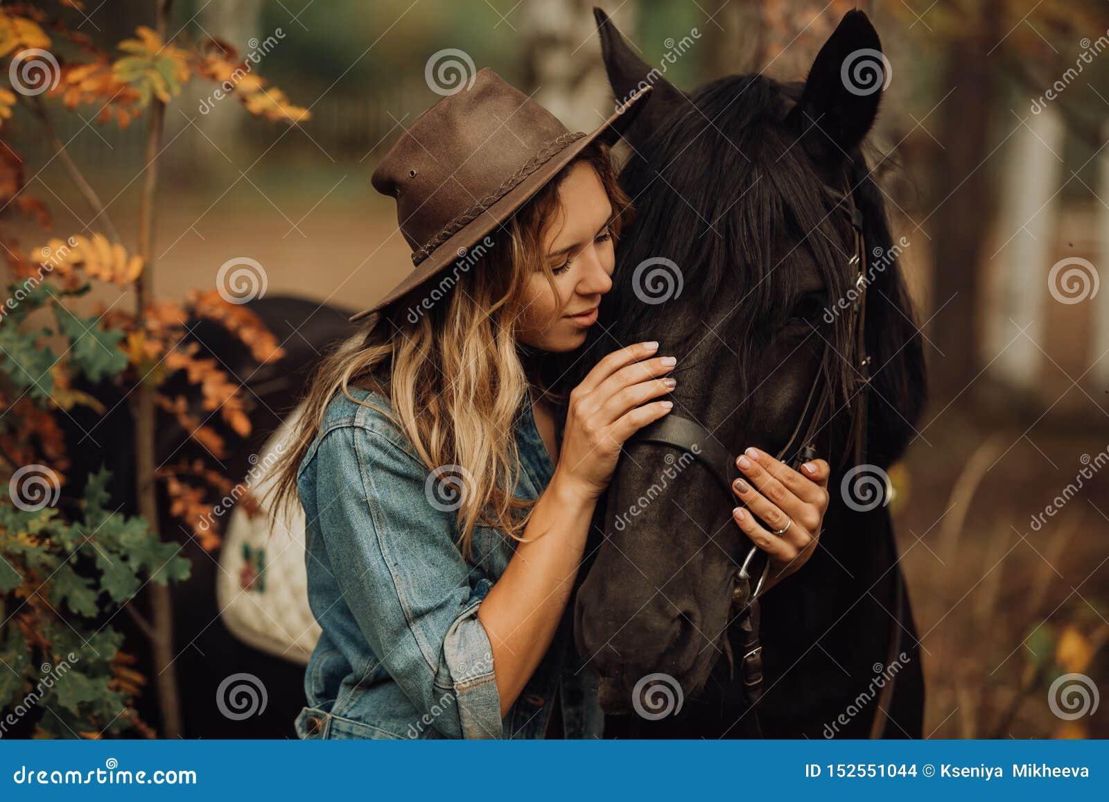 Hippie-Mädchen mit einem lächelnden Pferd im Wald