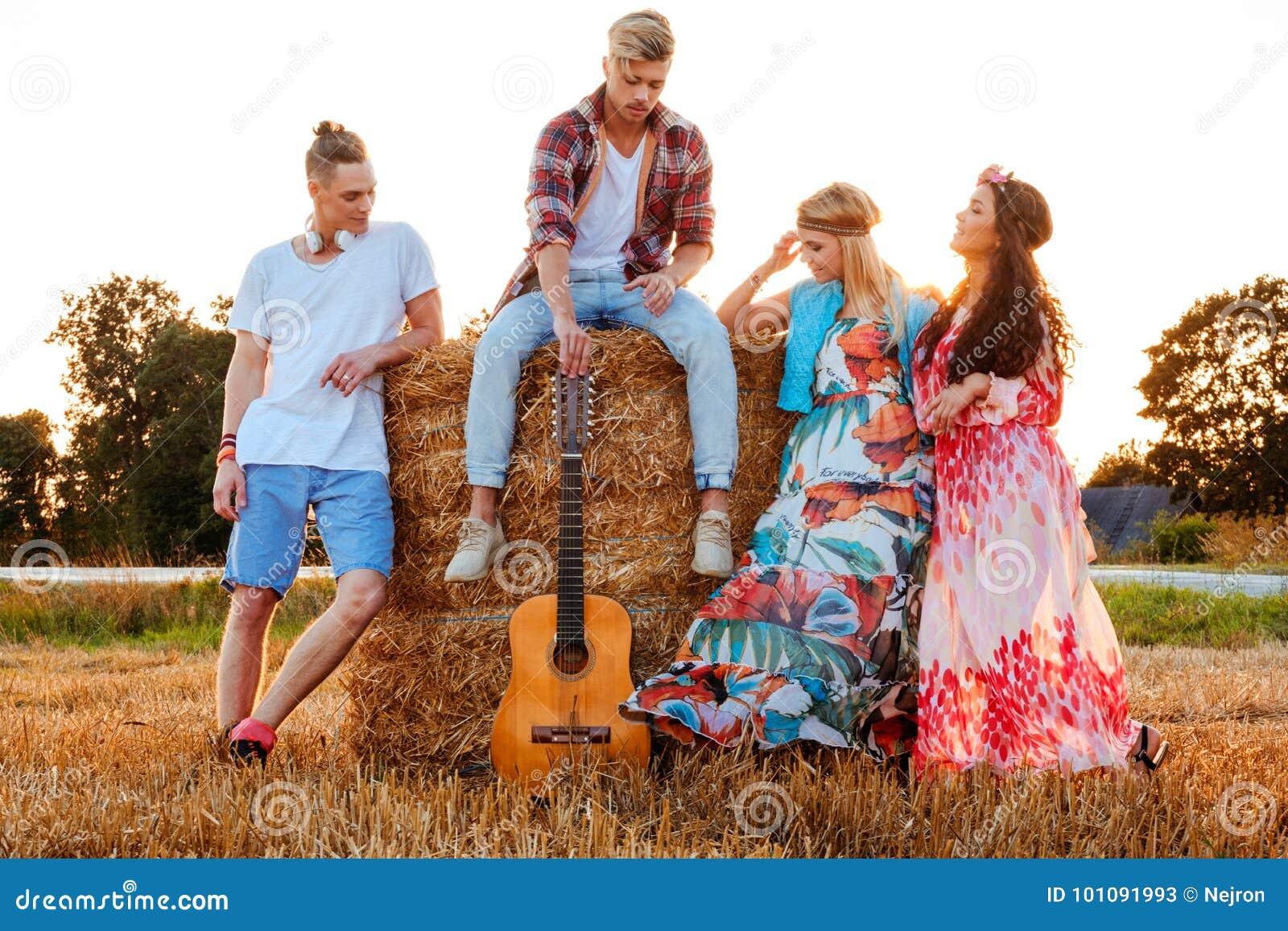 Hippievänner med gitarren i ett vetefält
