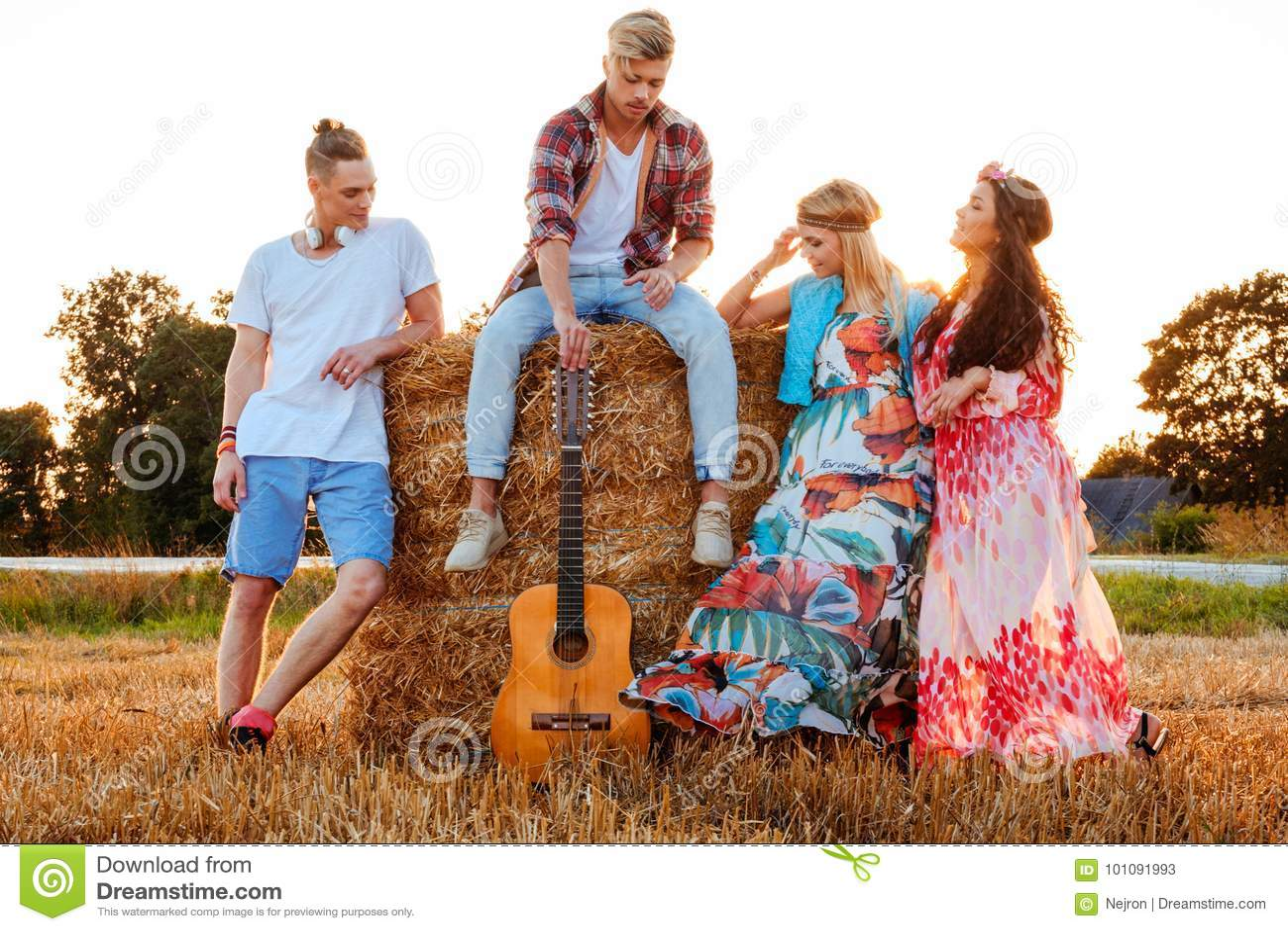 Hippievrienden met gitaar op een tarwegebied
