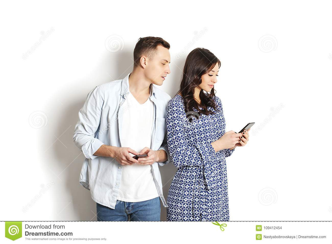 Jealous husband spying his wife mobile phone while she is reading a message. Technology & relationship concept. Modern romance tro